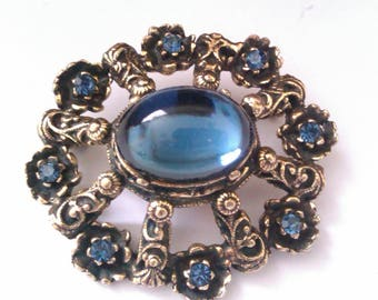 gold coloured dome shaped brooch