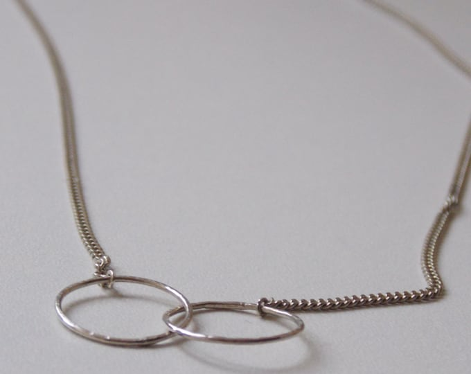 Silver necklace with 2 interlace ring.