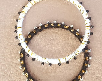 A set of Two Black, White and Gold Bangles