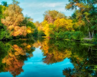 Reflection of luxurious autumn trees on the surface of a small lake