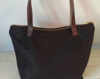 Dark brown waxed canvas handbag with brown leather handles zipped