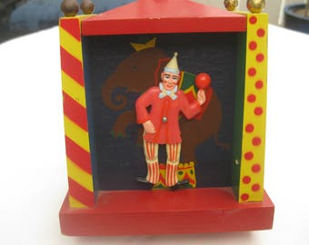 Antique wooden bank with musical wind up and dancing clown