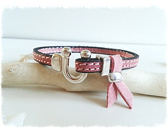 Pink leather strap with buckle.