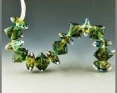 a set of 15 sparkling beads in a blend of green blue and amber encased in clear handmade lampwork glass - Bayou