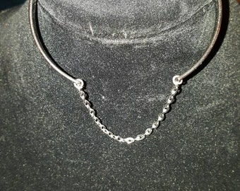 Silver colored cuff bracelet with small sized chain