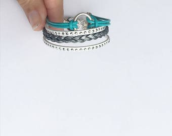 leather braided bracelet with a splash of turquoise. lobster clasp chain closure. infinity circle charm.