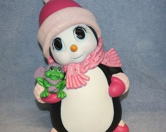Handpainted ceramic Penguin Holding a Frog and decked out in a pink scarf & matching hat