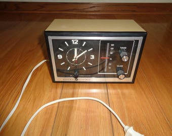 Vintage Mid Century Modern Style Electric Alarm Clock Radio in working condition with AM Stations only in great vinyl plastic box container