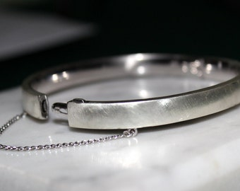Vintage Sterling Silver oval hinged bangle with safety chain.brush finish -8 inch circumference-hallmarked- secure hinge