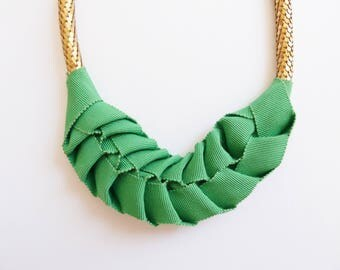 Necklace plastron with green ribbon  and tube of scales in golden brass