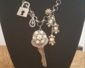 Vintage assemblage charm necklace. Steampunk padlock and key, old rhinestone brooch parts, and upcycled turquoise charm.