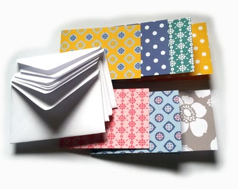 A set of 7 small white envelops and colourful patterned cards