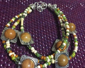 Wood grain beaded bracelet with tan and green glass beads. 7.5 inch