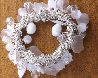 Winter white charm bracelet with lots of glass beads on a silver-plated elastic bracelet