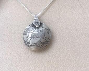 "Sterling silver ""wild horse"" reversible lentil bead pendant."