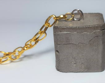 Black concrete cube with gold chain