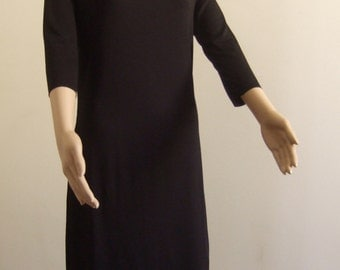 The p'tite short black sheath dress with long sleeves and her cleavage cleft
