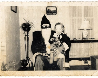 Vintage photo 1950 BAby Girl Sits on Black Face Santa Claus Lap Eerie Abstract Scary Mask FAce