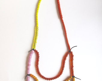 Long beaded necklace with red, orange, pink and yellow glass beads on black leather cord An Astrid Endeavor Spring and Summer fashion