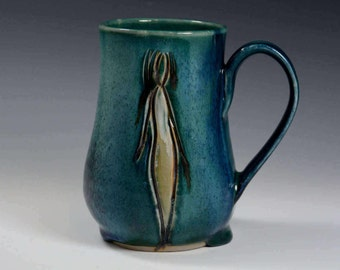 Pottery coffee cup with figure.