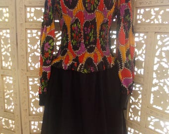 Vintage 60s Mod style mini dress in a crazy print bodice teamed with black & has a shirred top and sleeves, so will fit a variety of sizes.