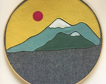 Embroidery Hoop Art,  Wall Art, Felt, Mountains, Mountain Range, Yellow, blue, green, and pink sun with grey linen