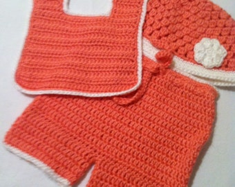 Crochet baby short pants, hat adorned with a flower and bib.