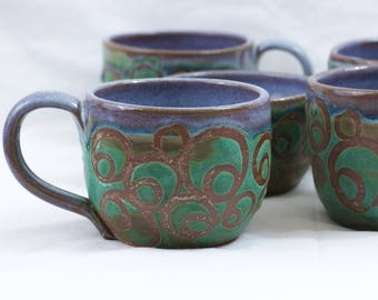 Wheel-thrown mugs with circles, weathered bronze and opal glazes