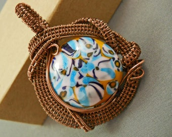 Moretti glass bead decorated in yellow, blue and white, wrapped in oxidized copper wire pendant