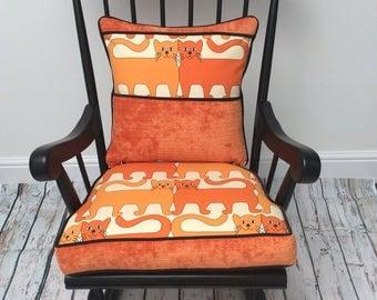Black vintage rocking chair with orange cat cushions