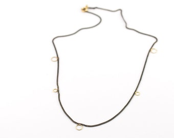 Silver necklace with golden clasp and details. Made from recycled material.