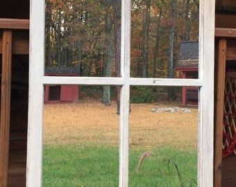 Storm window repurposed into a mirror