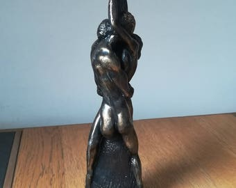 Loving couple wax sculpture in black and gold.