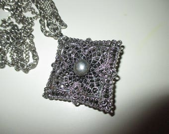 A pendant necklace with the name Celebrity and a pattern number--silvertone with a double chain-pendant is 2 sided