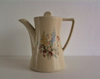 Beautiful old, cream-colored coffee pot with floral decor, vintage mid century