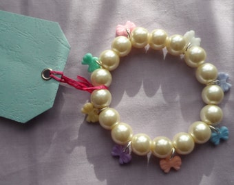Womens white tint elastic pearl charm bracelet with yellow, mint, pink, white, lilac, blue, peach and purple pastel bows. Girls, jewellery.