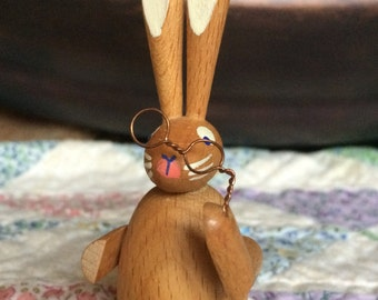 Wooden rabbit w holding spectacles.