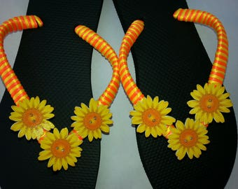 Black flip flops with yellow and orange satin ribbon and yellow flowers.  Summer black, yellow and orange flip flops with yellow  flowers.
