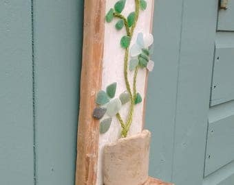 Sea glass flowers in sea pottery vase on driftwood