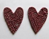 a pair of plum colored embossed ceramic hearts