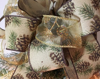 Lg Xmas tree topper bow sheer gold w/ pinecone design glitter ribbon, and a burlap ribbon w/pinecones, evergreen branches, gold trim