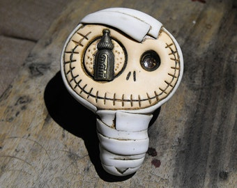 Cute baby mummy brooch in dirty white. Creepy and cute skull with a feeding bottle in his eye.