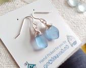 Sea Glass hook earrings of light blue drops suspended from sterling silver hooks