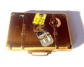 Vintage metal suitcase compact with hotel travel decals