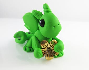 Polymer clay bright green baby dragon with a flower