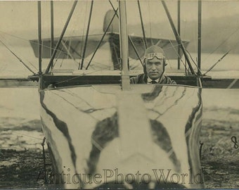 Handsome pilot posing in plane antique photo