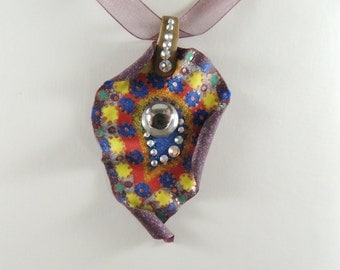 Curled paisley polymer clay pendant with swarovski flat back crystals on a burgundy organza ribbon with bronze coloured end covers.