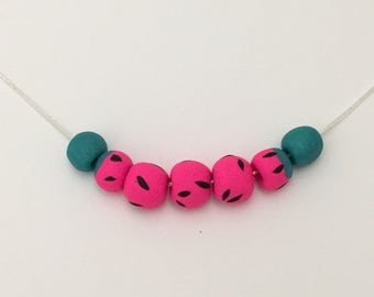 Watermelon inspired clay bead necklace on silver snake chain.