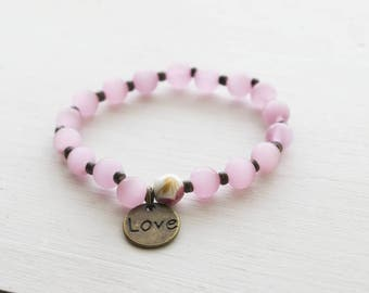 Pink glass stretch bracelet with rose accent