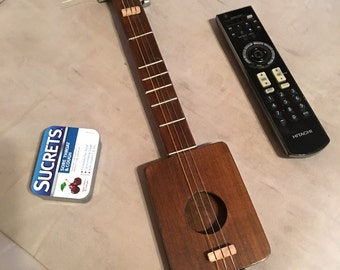 "Guitar hand crafted 3 string  18"" long sounds very good and loud for a small guitar"